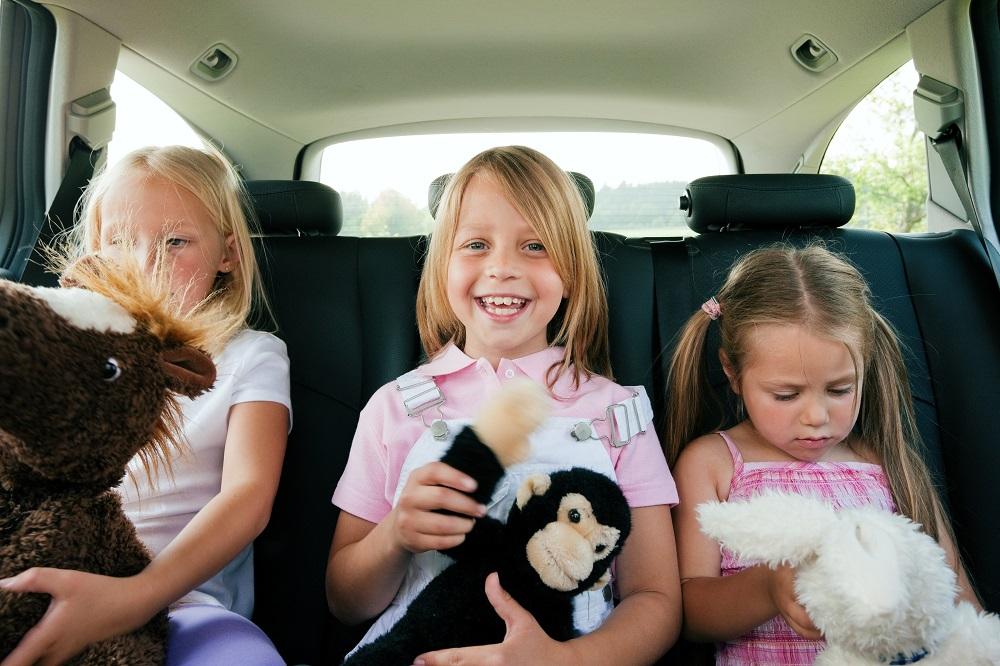 jeunes filles jouant avec des peluches à l'arrière d'une voiture