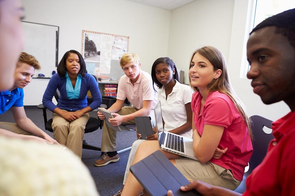 groupe de lycéens discutant dans une salle de classe bilingue